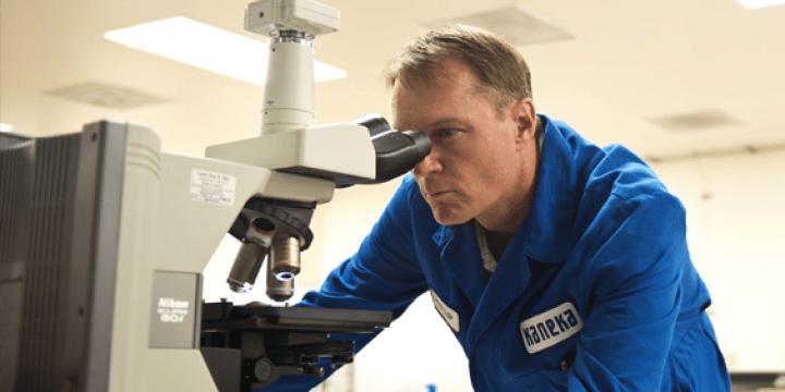 A man in a Kaneka lab uniform looks through a microscope
