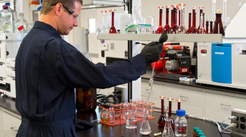 A man in protective lab gear uses a pipette to test ingredients for Kaneka products